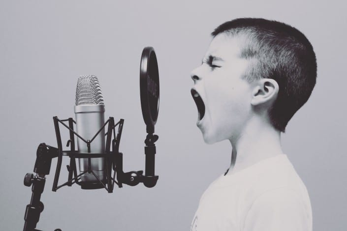 boy singing at microphone, branding educațional, singing